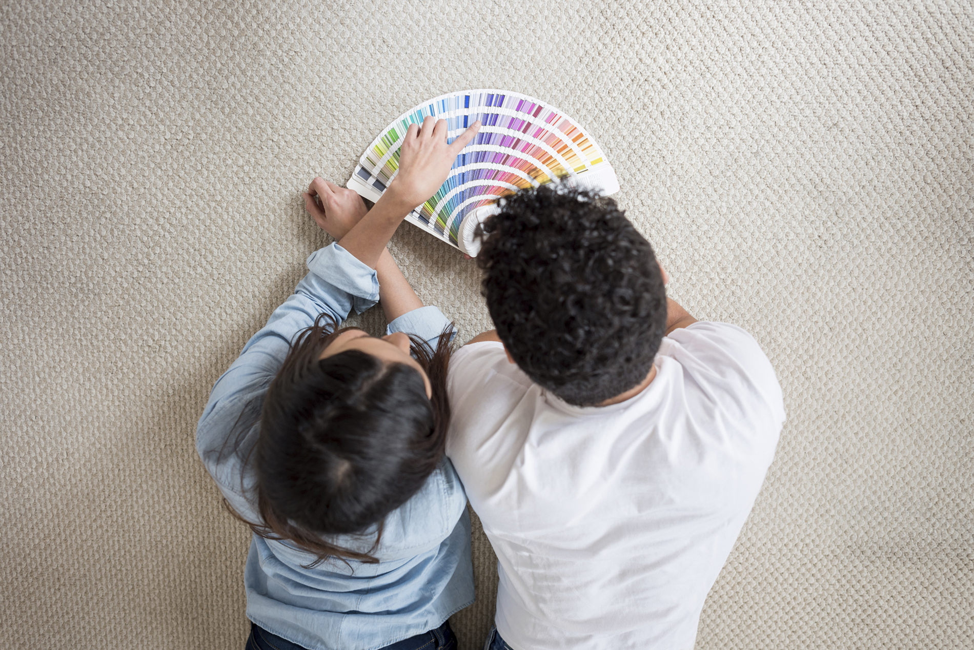 Loving couple painting their house and looking at the colors