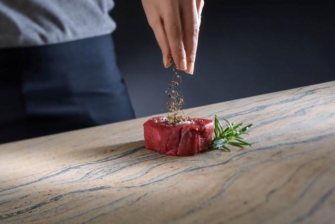Küchenarbeitsplatte aus Naturstein, auf der ein Steak gewürzt wird.