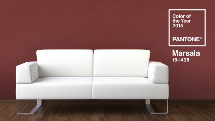 Eine helle Couch vor einer Wand in der Farbe Marsala.