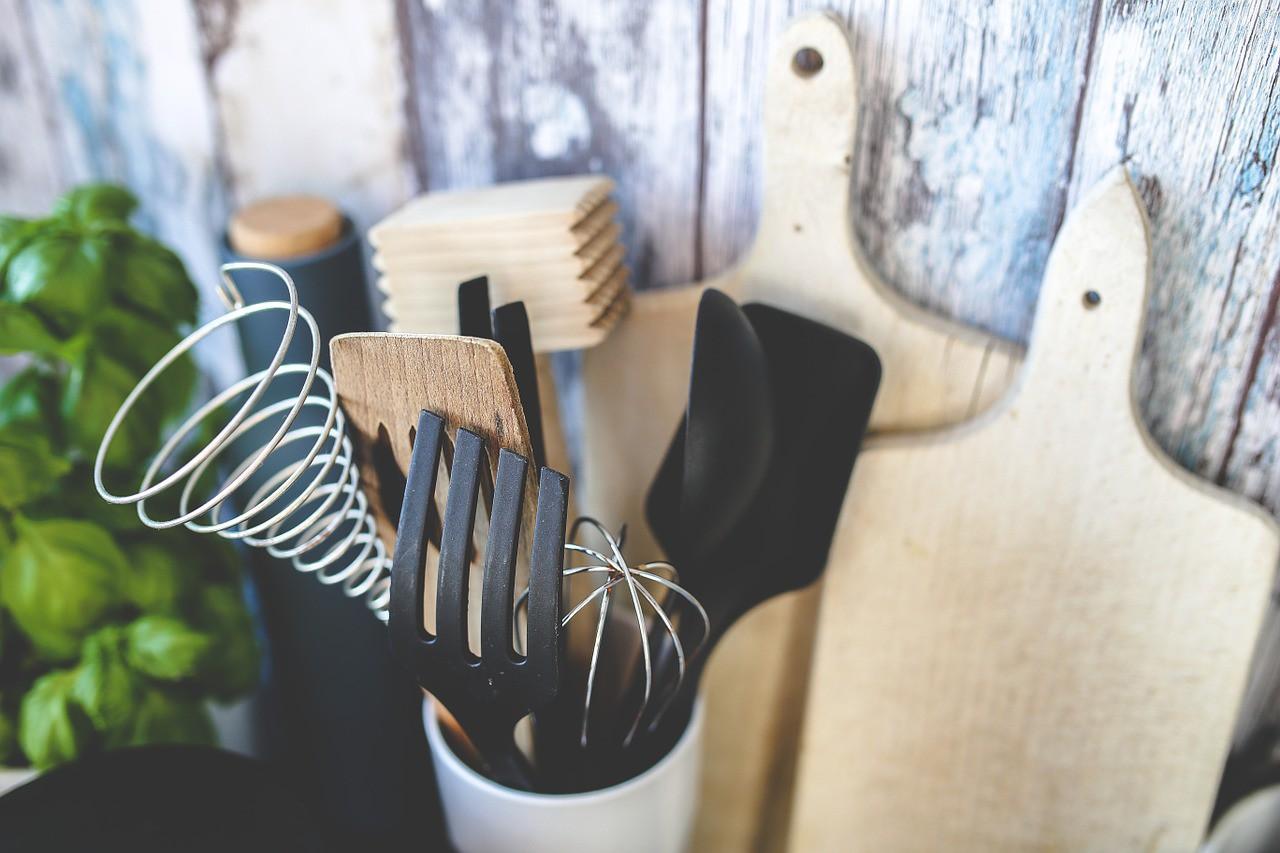ein Basilikumtopf, ein schwarzes Gefäß mit Korken, zwei Holzbretchen und ein weißes Gefäß mit Küchenhelfern vor einem Hintergrund aus Holz.