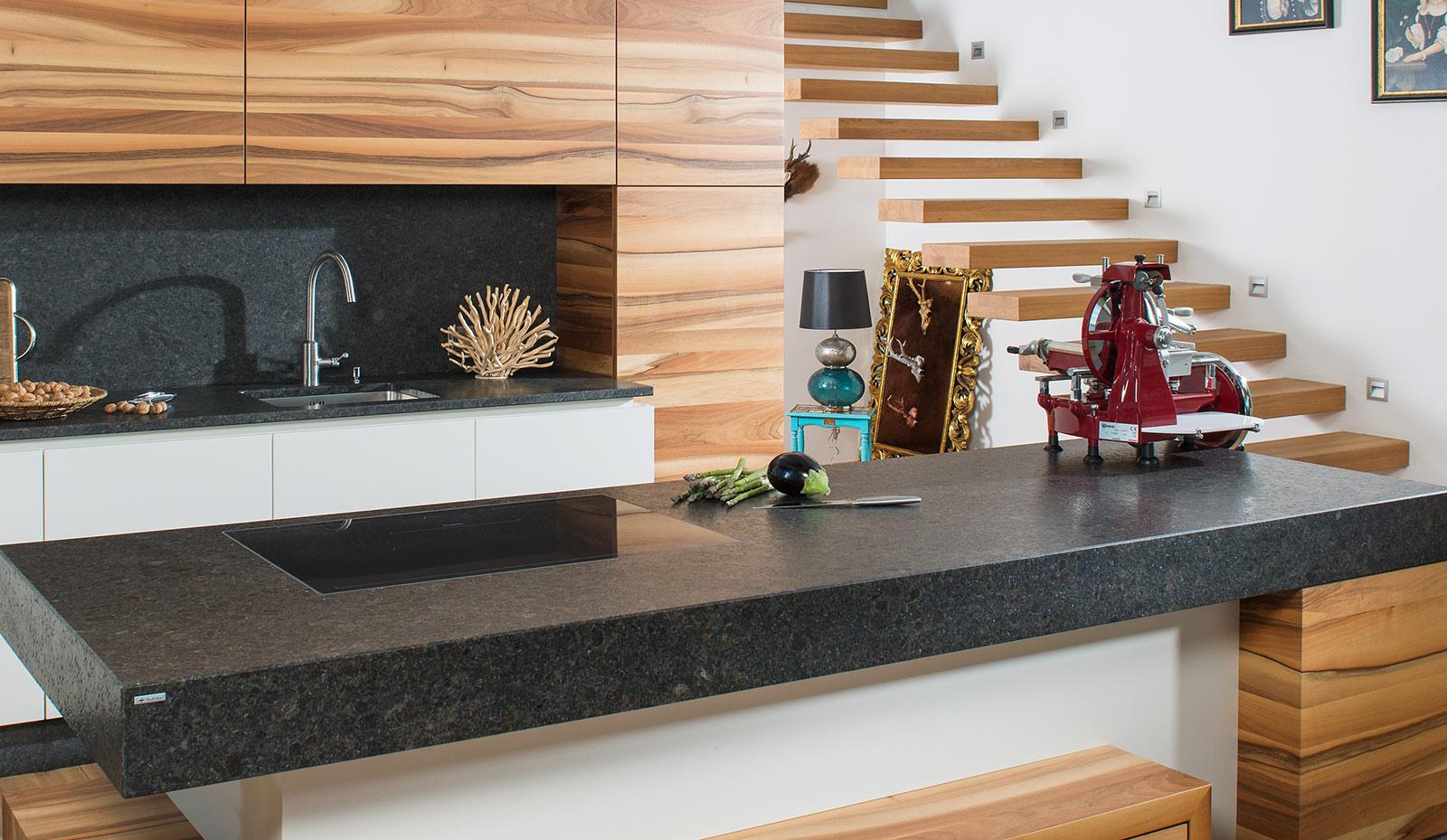 Offene Wohnküche mit Holzakzenten und Küchenarbeitsplatte aus Naturstein.