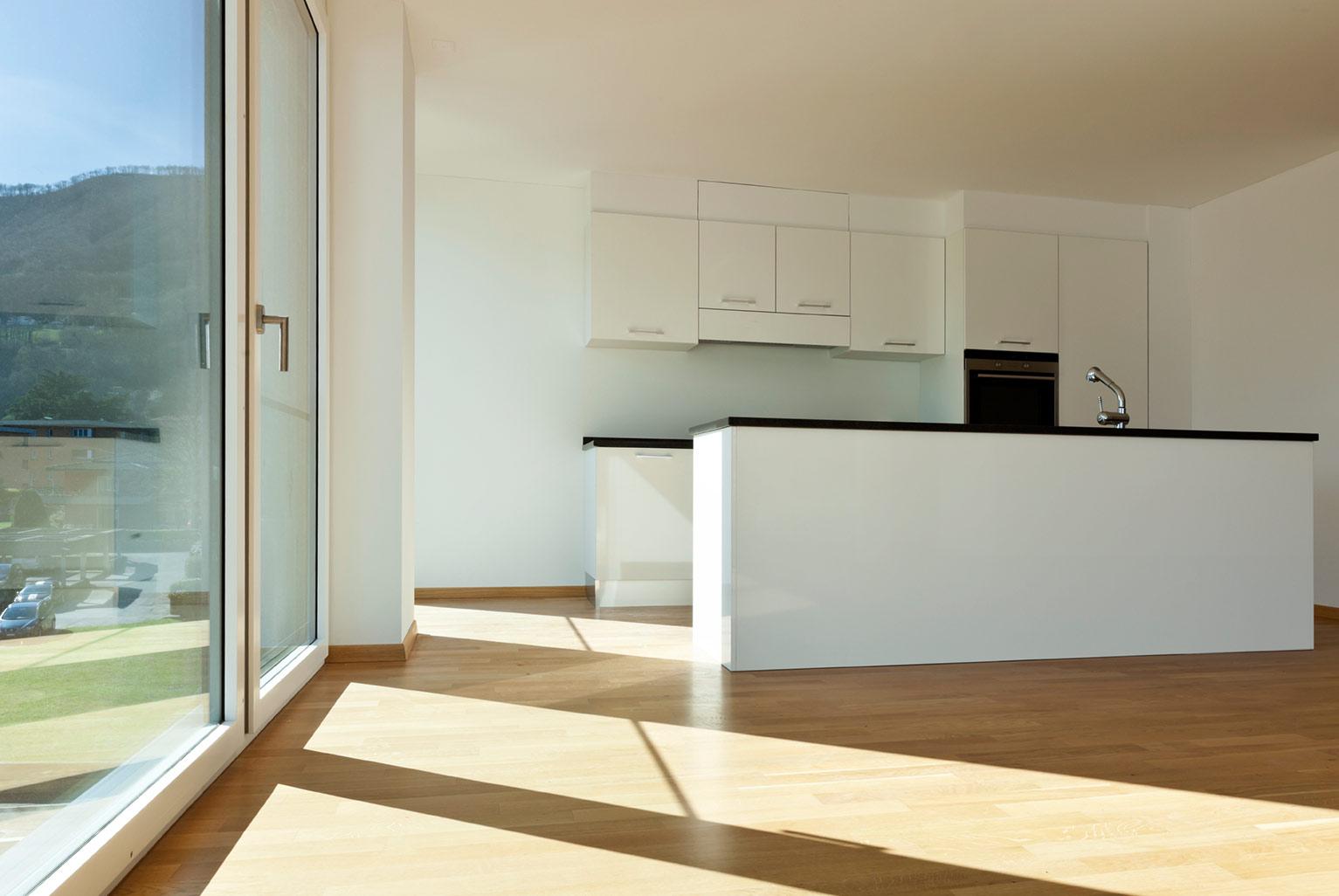 Weiße Küche in einem leeren Raum mit großer Fensterfront.