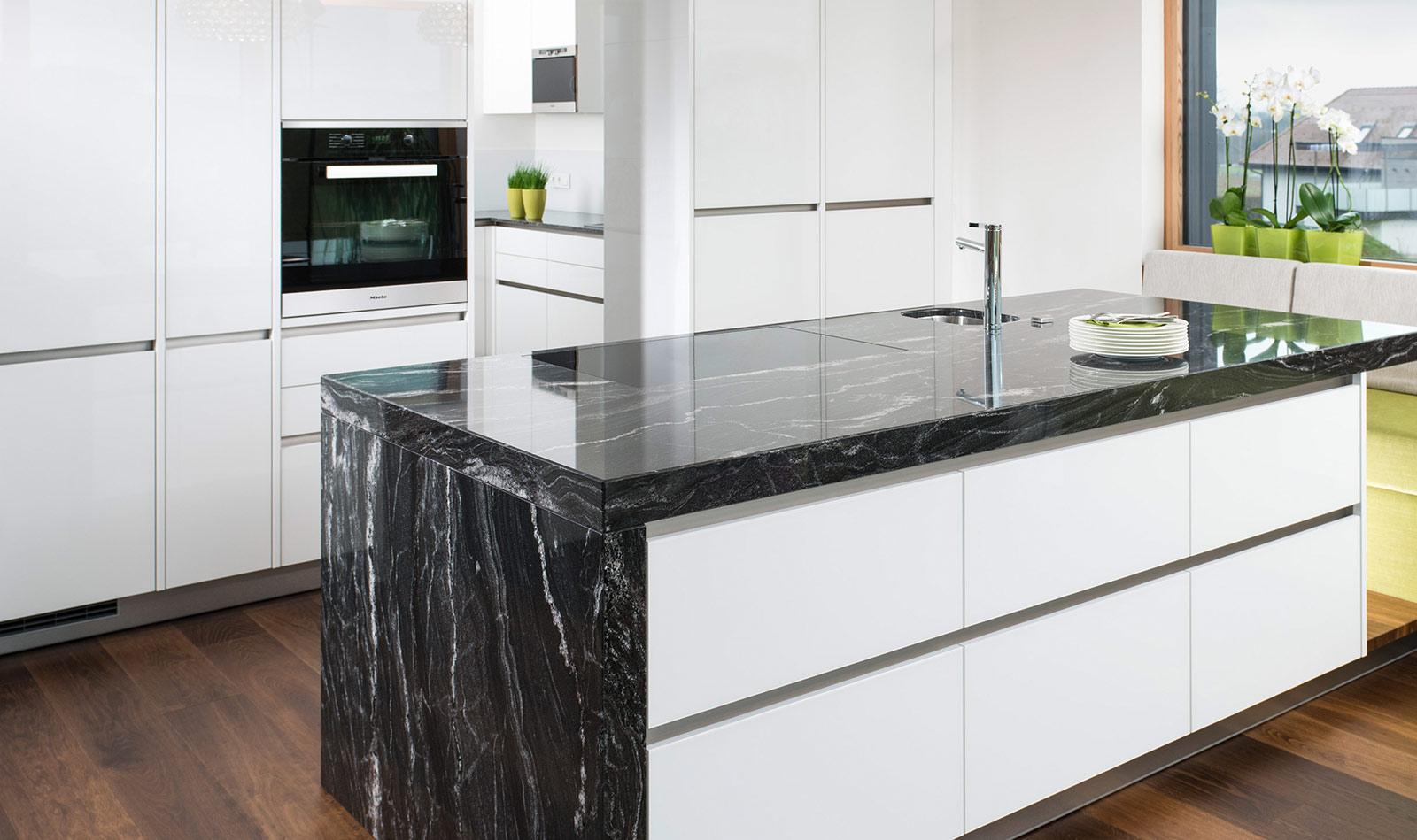 Küche mit weißen Möbelfronten und einer Kücheninsel in schwarz-weißem Naturstein.