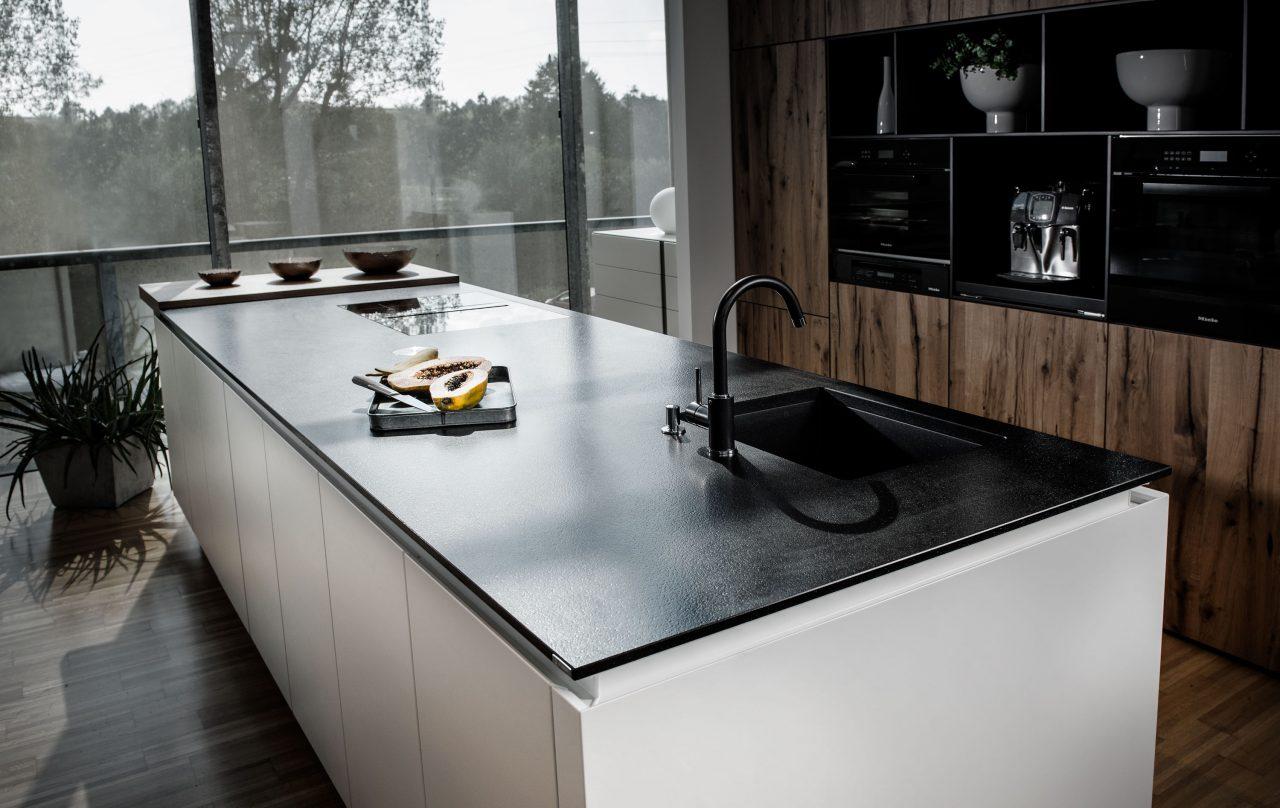 """Küchenarbeitsplatte aus Naturstein """"Nero Assoluto"""" auf einer weißen Kücheninsel. Im Hintergrund Einbaubacköfen."""