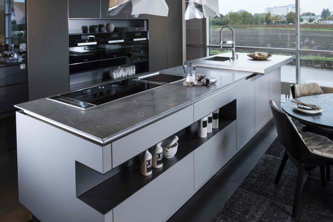 Offene, moderne Küche mit einer Arbeitsplatte aus grauem Naturstein und matten Küchenfronten.