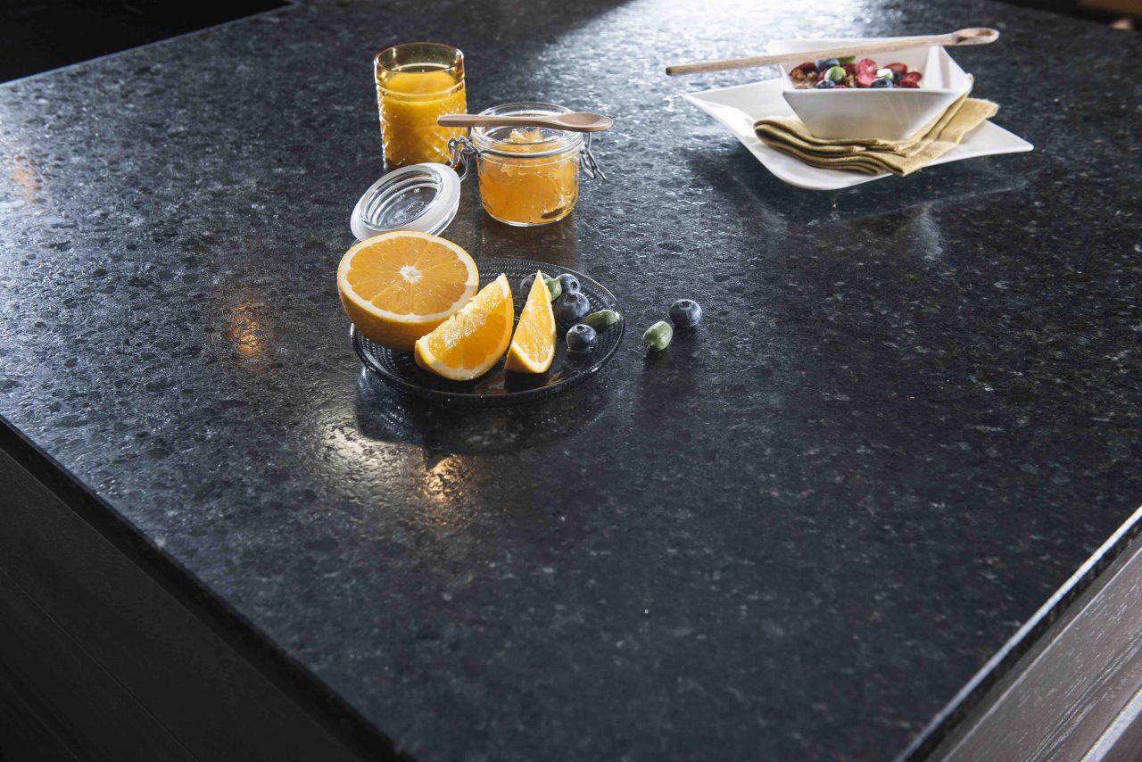 Küchenarbeitsplatte aus dunklem Naturstein, mit einer aufgeschnittenen Orange, Heidelbeeren und Oliven darauf.