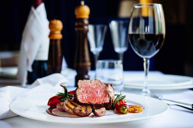 Eingedeckter Tisch mit Pfeffermühlen, einem Glas Rotwein und Steak mit gegrilltem Gemüse auf einem weißen Teller.