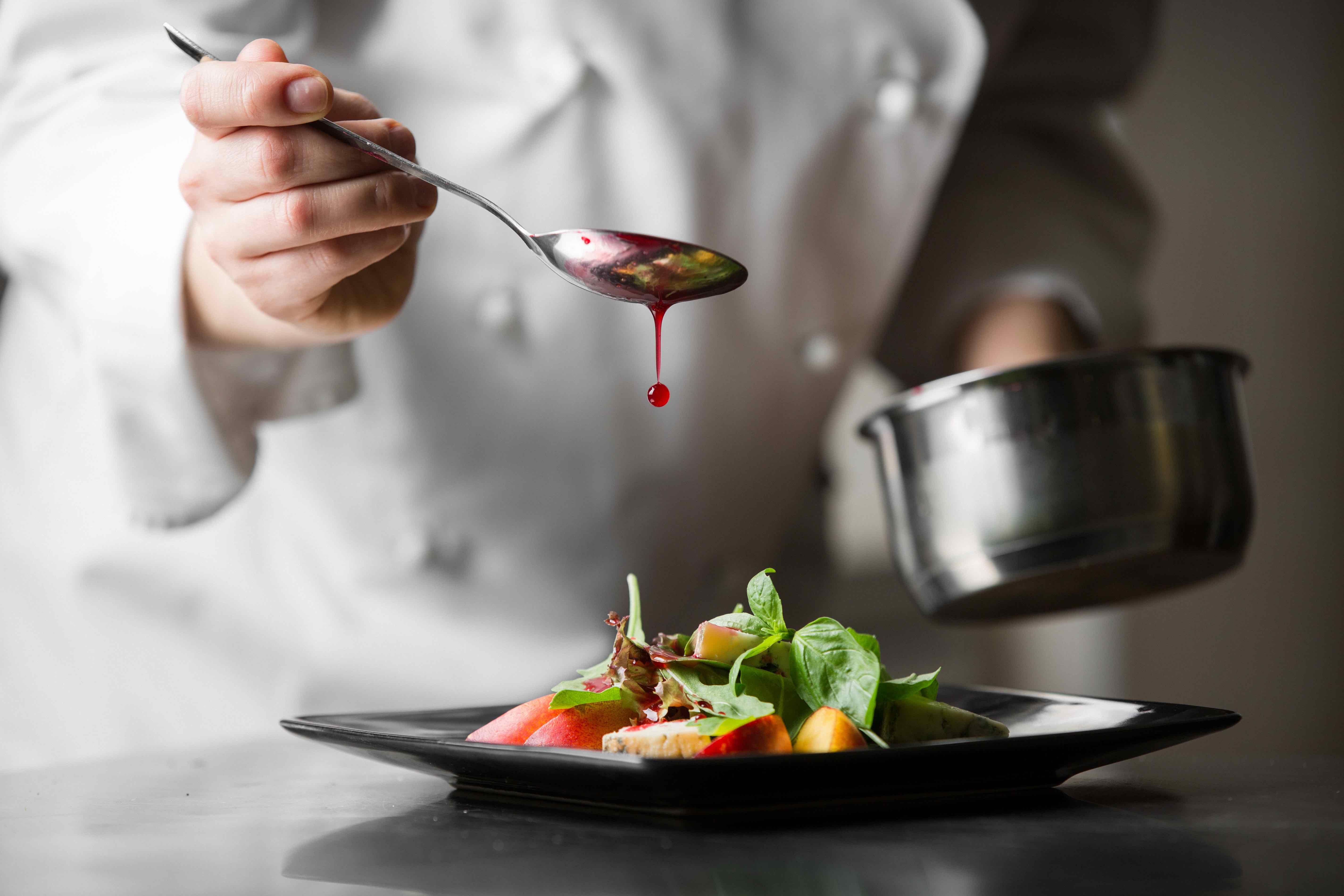 Koch beim Anrichten eines Gerichtes.