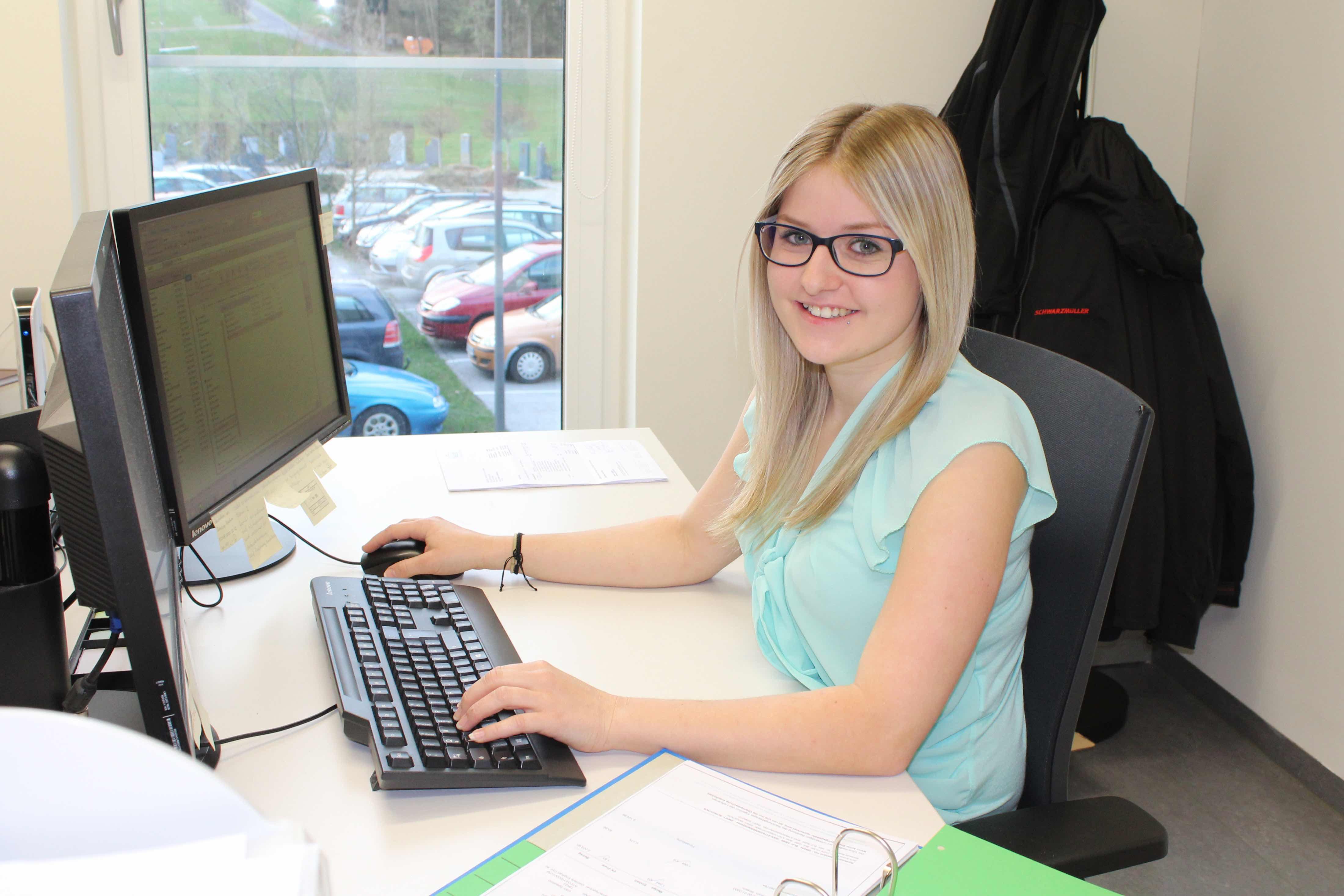 Eine Frau sitzt am Schreibtisch vor dem Computer.