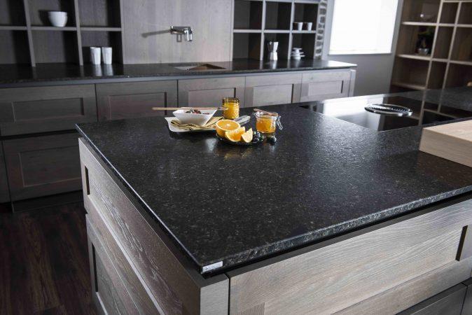 Küche aus Holz mit Küchenarbeitsplatte aus dunklem Naturstein, mit einer aufgeschnittenen Orange, Heidelbeeren und Oliven auf der Kücheninsel liegend.
