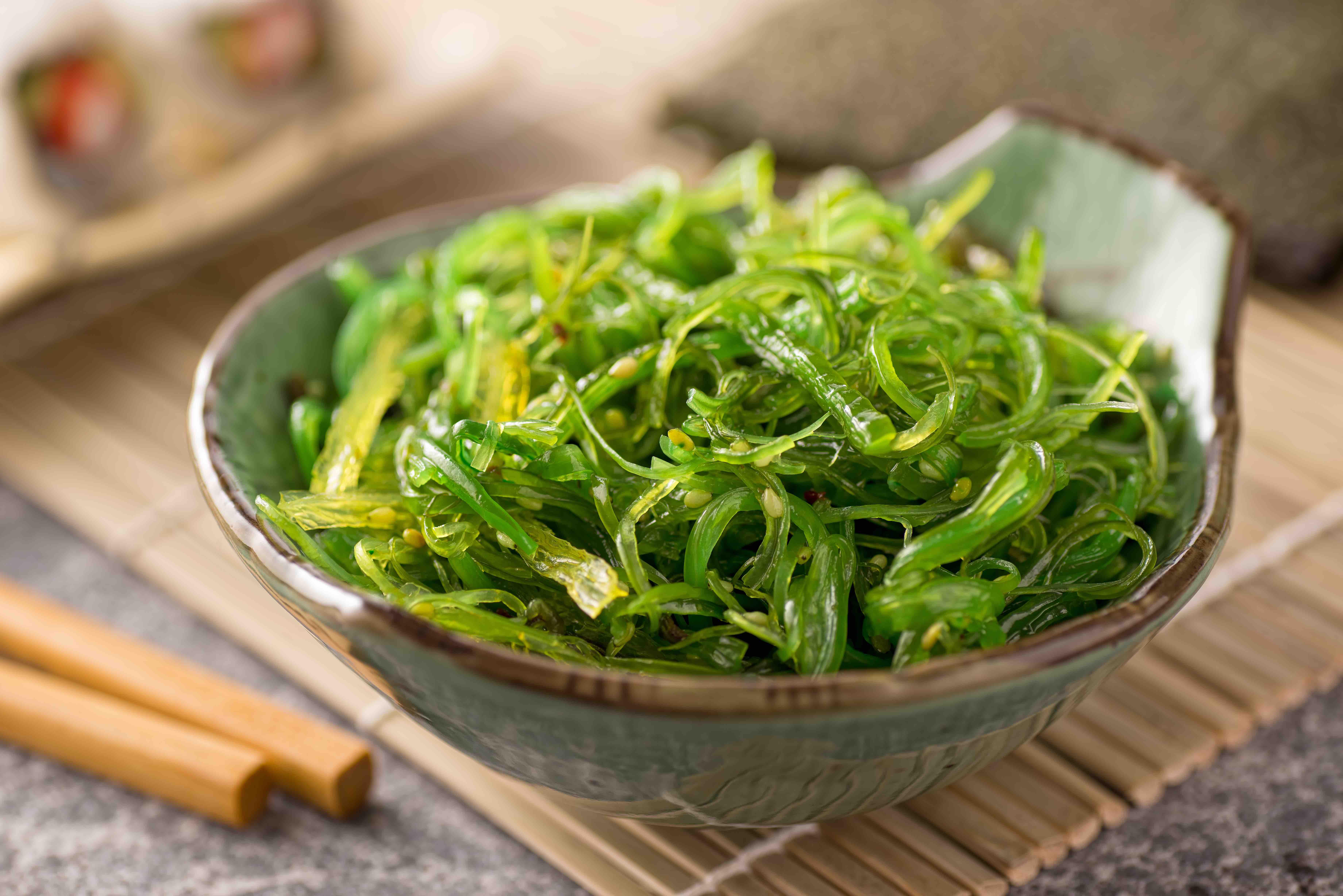 Schale mit grünem Algen-Salat, auf einer Bambusmatte. Daneben liegen Essstäbchen.