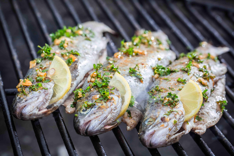 Gegrillte Fische auf dem Grillrost, mit Zitronenscheiben gespickt und mit Kräutern gewürzt.