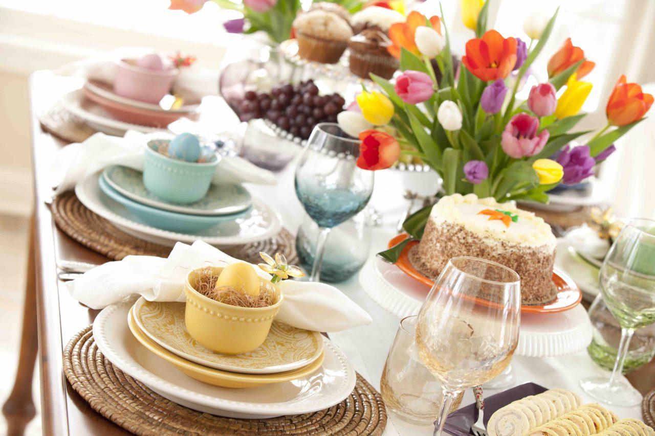 Gedeckter Ostertisch mit pastellfarbenem Geschirr, Platzsets aus Korb, Stoffservietten und gefärbten Eiern. Auf dem Tisch steht eine Vase mit Tulpen, ein Karottenkuchen sowie eine Étagère mit Trauben und Muffins.