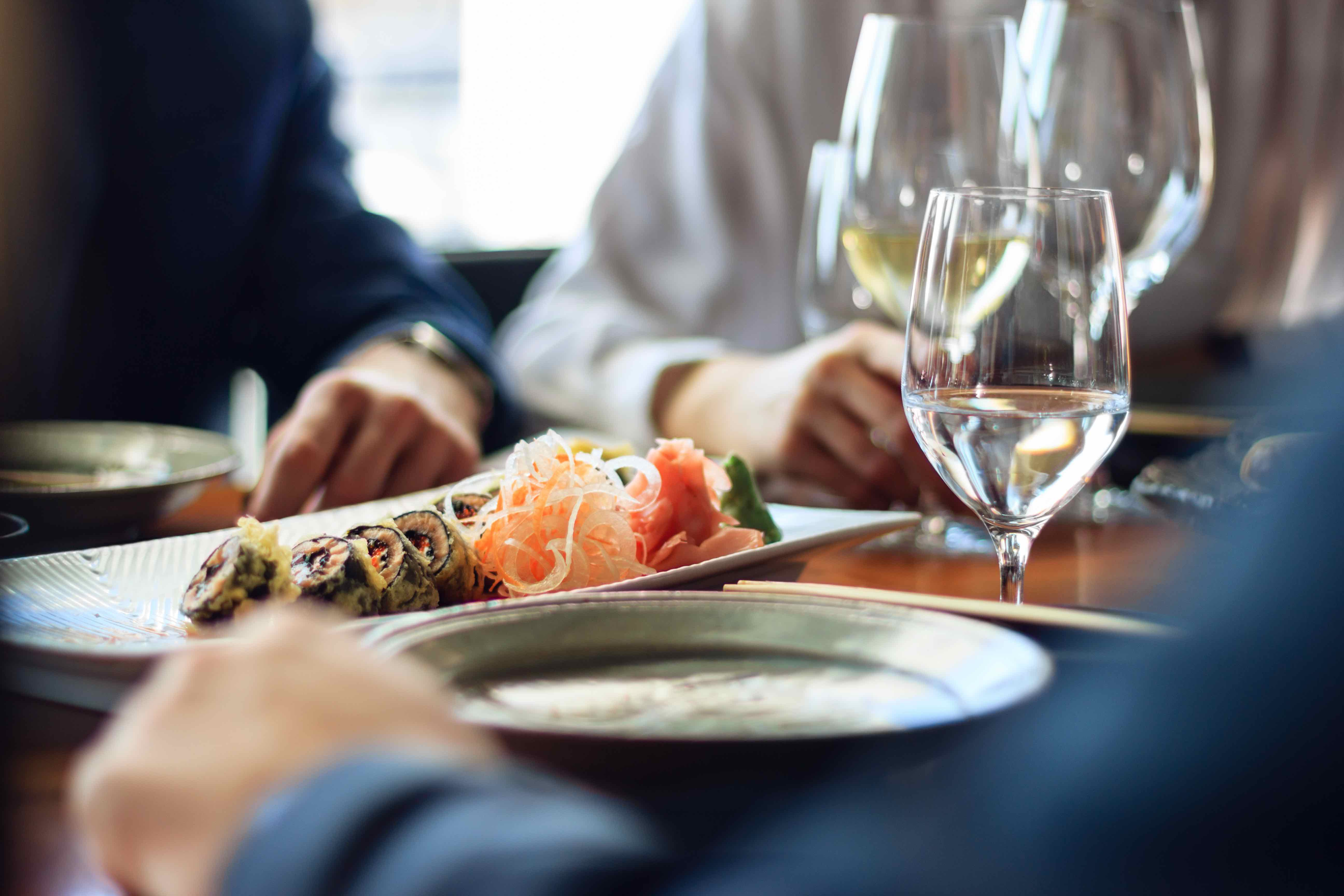 Gedeckter Tisch mit Wasser- und Weißweingläsern sowie weißer Sushi-Platte in der Mitte. Drei Personen sitzen am Tisch.