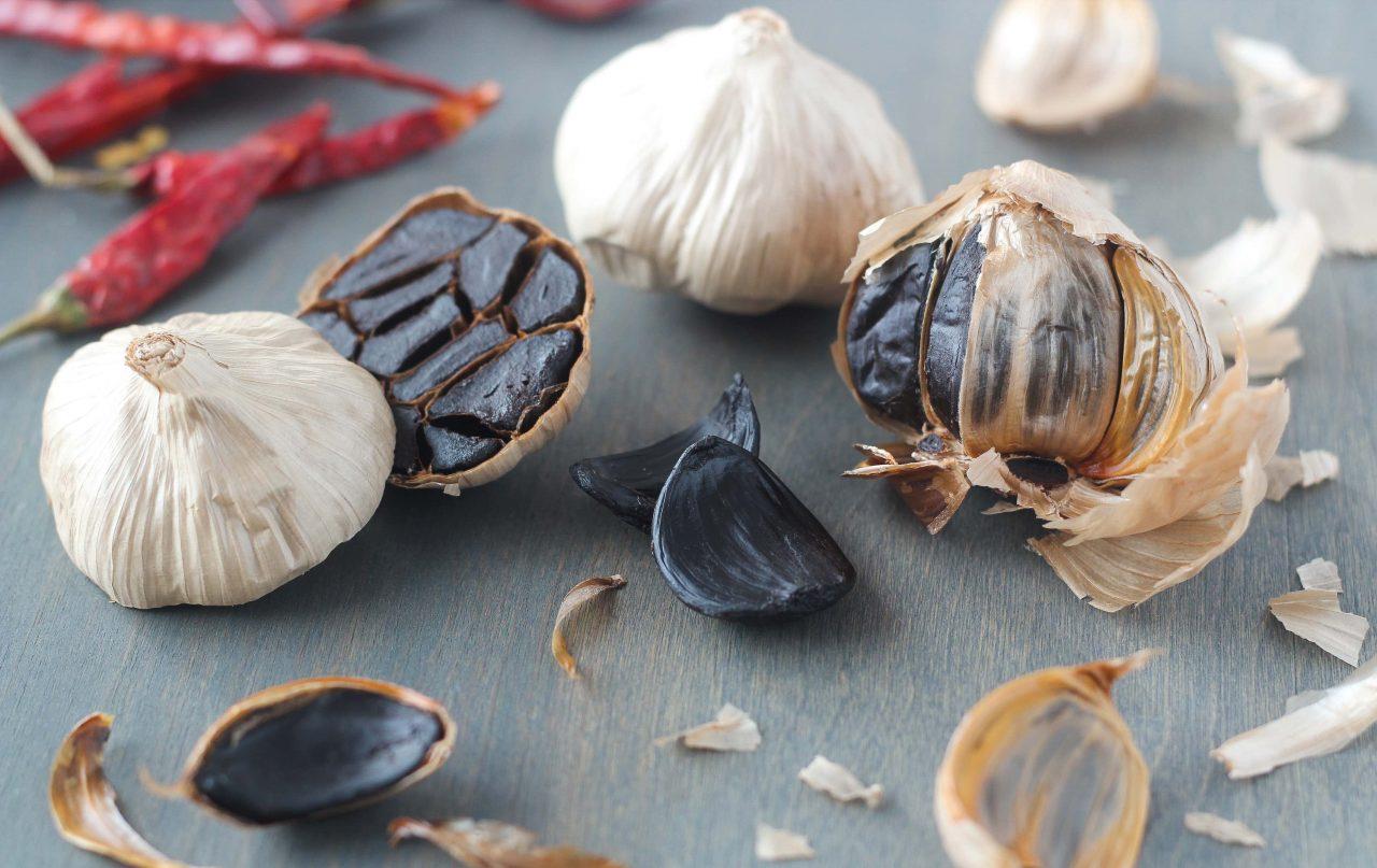 Schwarzer Knoblauch, ganze Knollen, eine quer aufgeschnittene Knoblauchknolle und einzelne Knoblauchzehen auf grauem Untergrund mit roten Chilischoten.