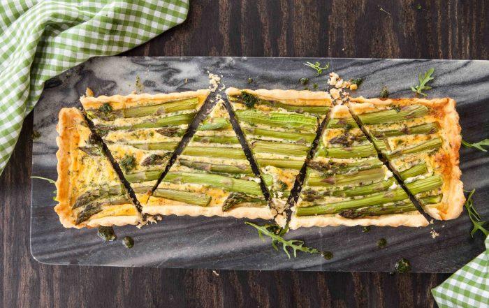 Rechteckige Quiche mit grünem Spargel auf einem Steintafel mit grün-weiß karierten Geschirrtüchern daneben.