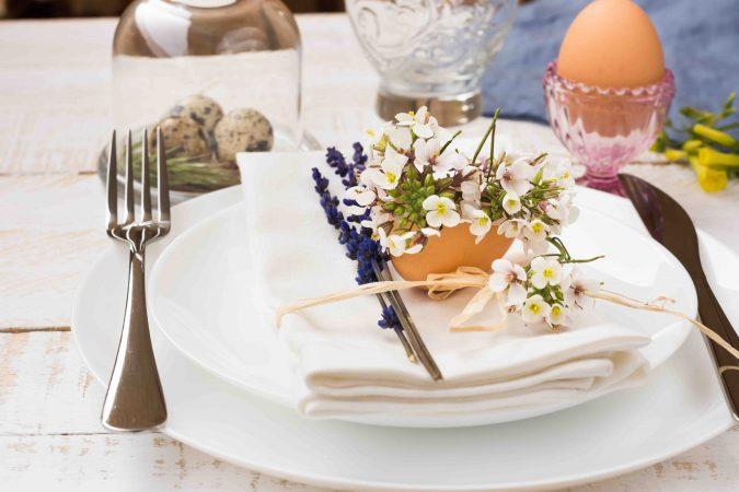 Weißer Holztisch mit weißem Geschirr, weißer Stoffserviette und Besteck. Auf dem Gedeck liegt eine Deko mit Eierschale, Lavendel und weißen Blumen. Auf dem Tisch stehen ein rosafarbener Glas-Eibecher mit gekochtem Ei darin sowie eine Glasglocke mit drei Wachteleiern darunter.