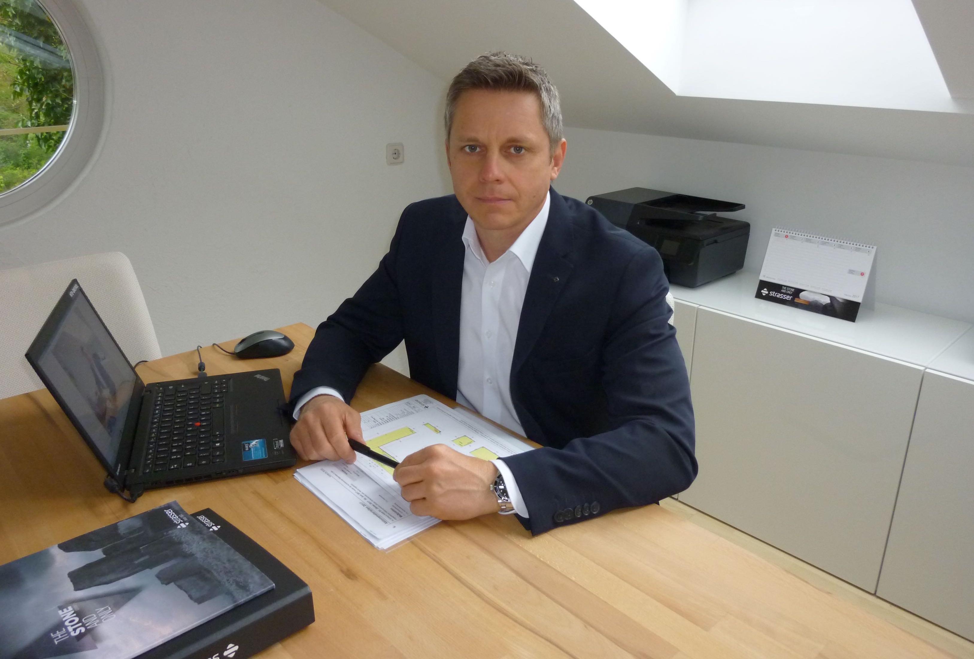 Mann mit weißem Hemd und dunklem Sakko, am Schreibtisch sitzend. Auf dem Schreibtisch liegen Unterlagen und ein Laptop.