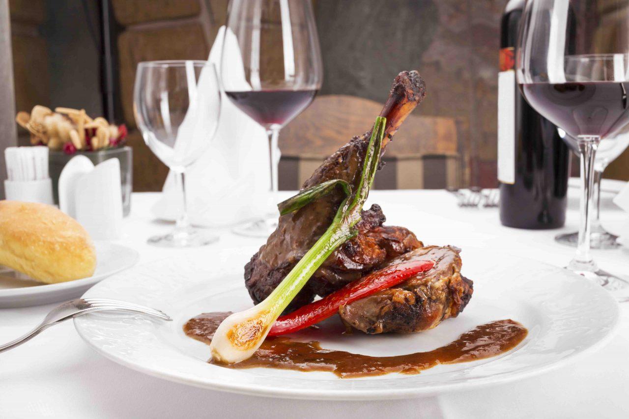 Lammkarree serviert mit Sauce, gegrillter Frühlingszwiebel und gegrillter, roter Paprika. Begleitet von Rotwein. Eingedeckt mit weißem Geschirr und einer weißen Tischdecke.