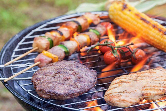 Kohlegrill mit brennenden Kohlen. Auf dem Grillrost liegen ein Maiskolben, Rispentomaten, Fleischspieße mit gelber und grüner Paprika, eine Frikadelle und Geflügel.