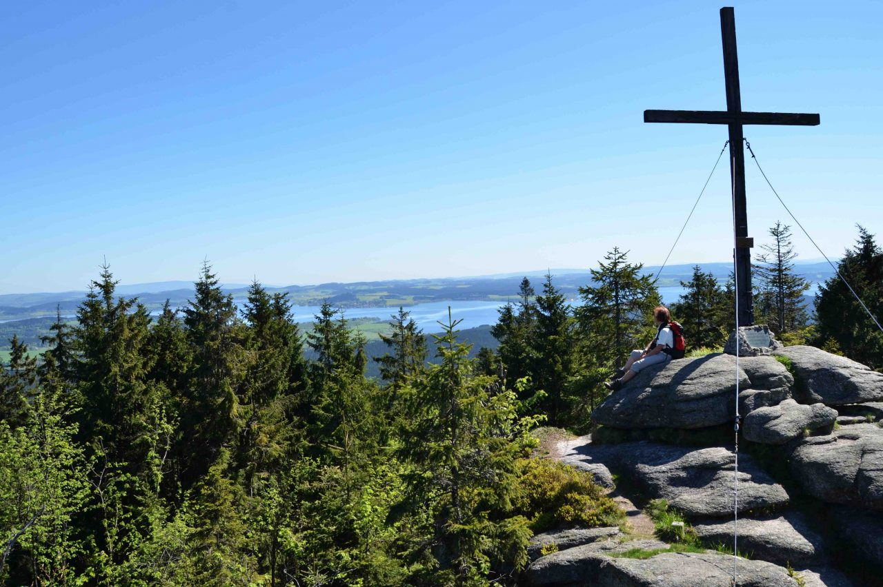 Eine Wanderin sitzt am Gipfelkreuz des Bärensteins mit Blick über das Mühlviertel