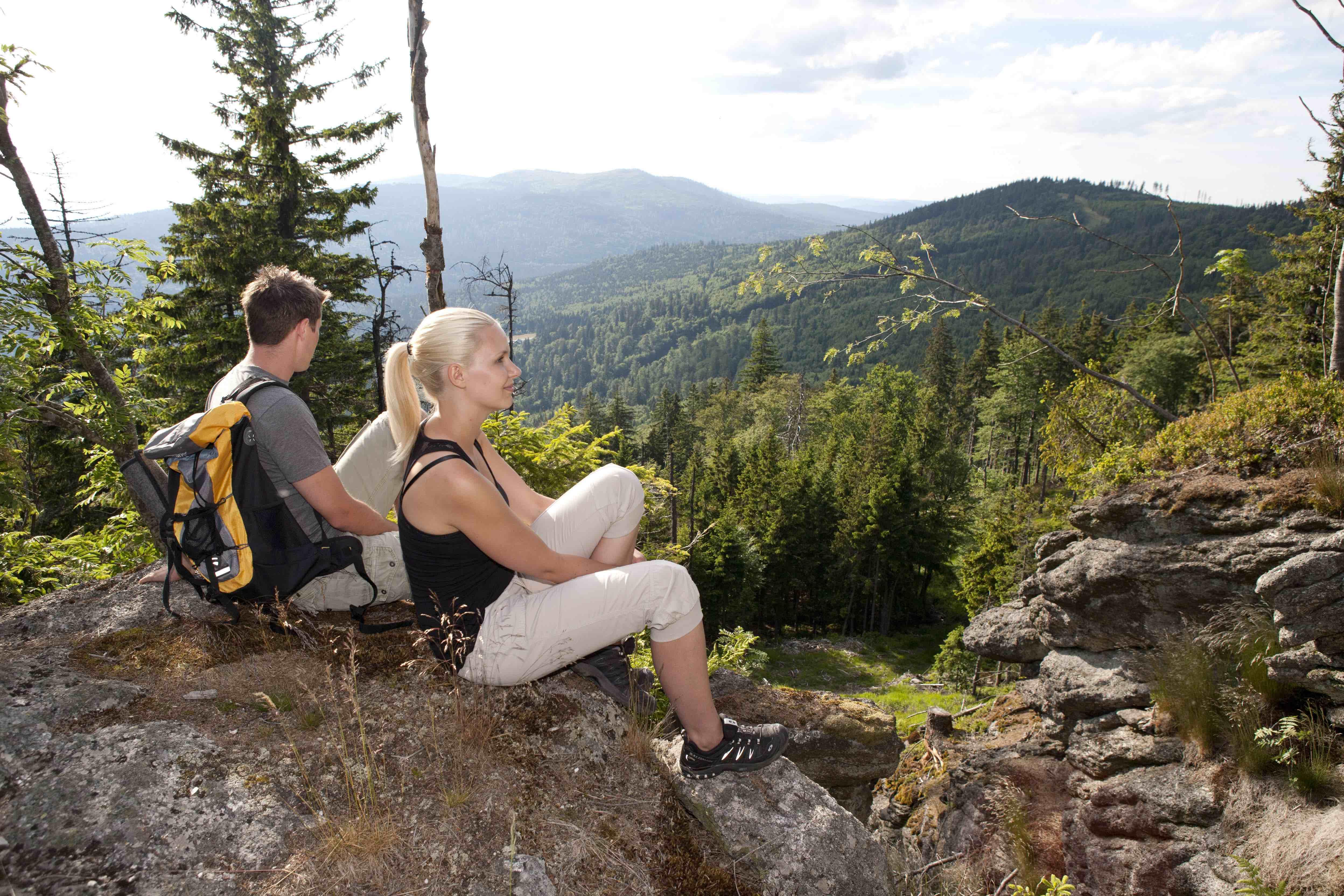 Zwei Wanderer sitzen auf einer Erhöhung mit Blick auf die Region Böhmerwald im Mühlviertel