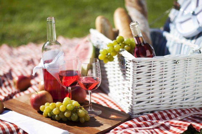 Rot-weiß karierte Picknickdecke auf der Wiese mit weißem Picknick-Korb, Baguettes, Weintrauben und Wein.