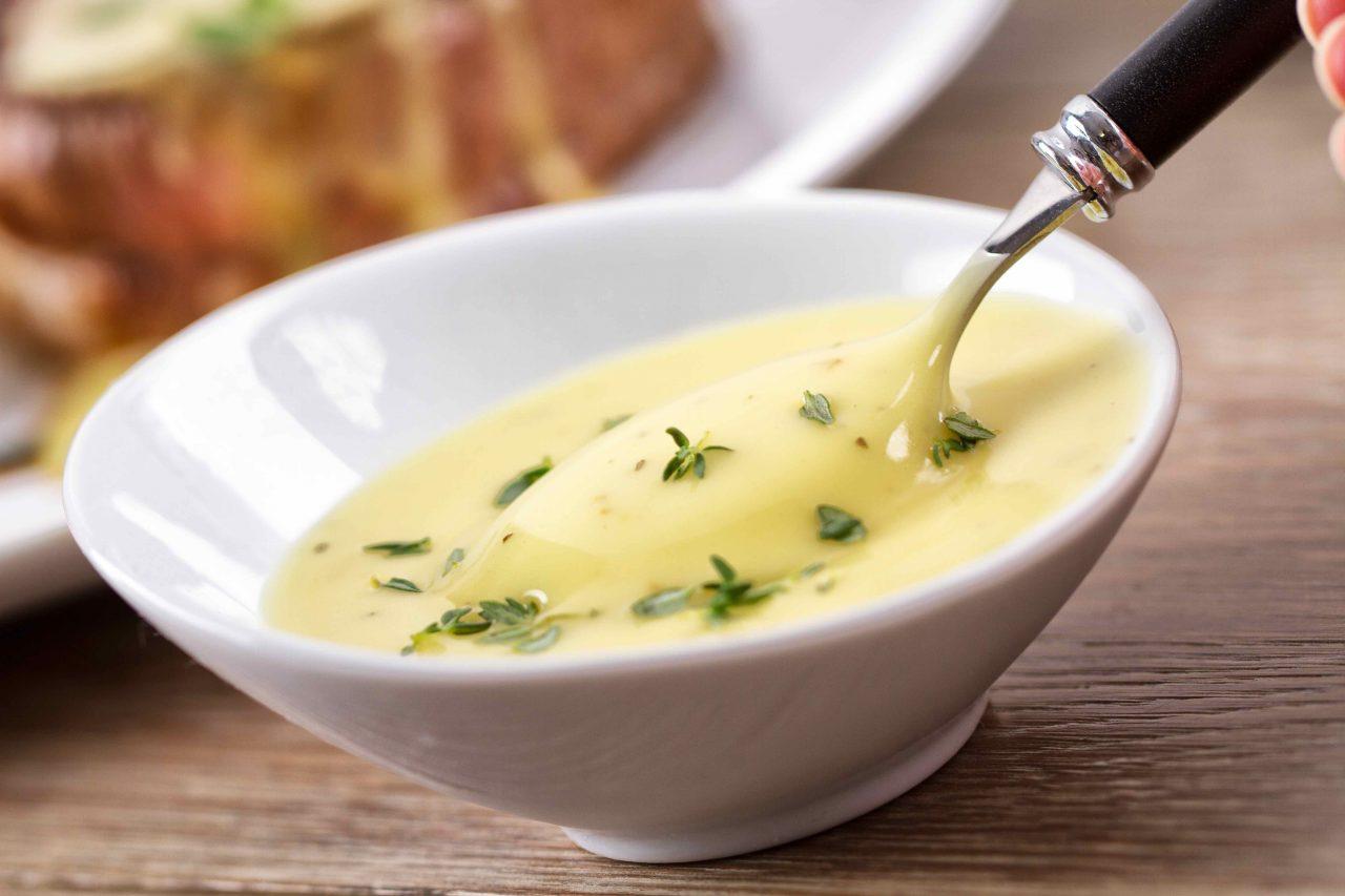 Sauce Bearnaise in einem weißen Schälchen mit Löffel.