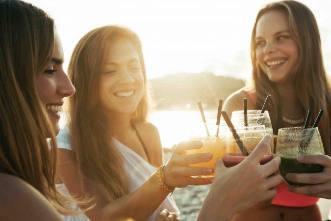 Drei Frauen stoßen bei Sonnenuntergang mit Cocktails an.