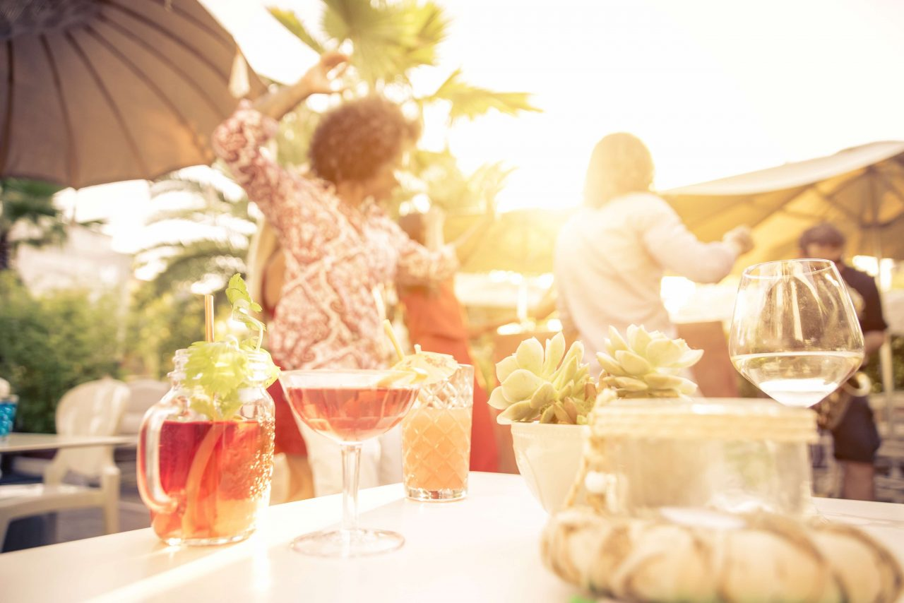 Tisch im Sonnenlicht mit verschiedenen Sommergetränken. Im Hintergrund tanzen Leute.