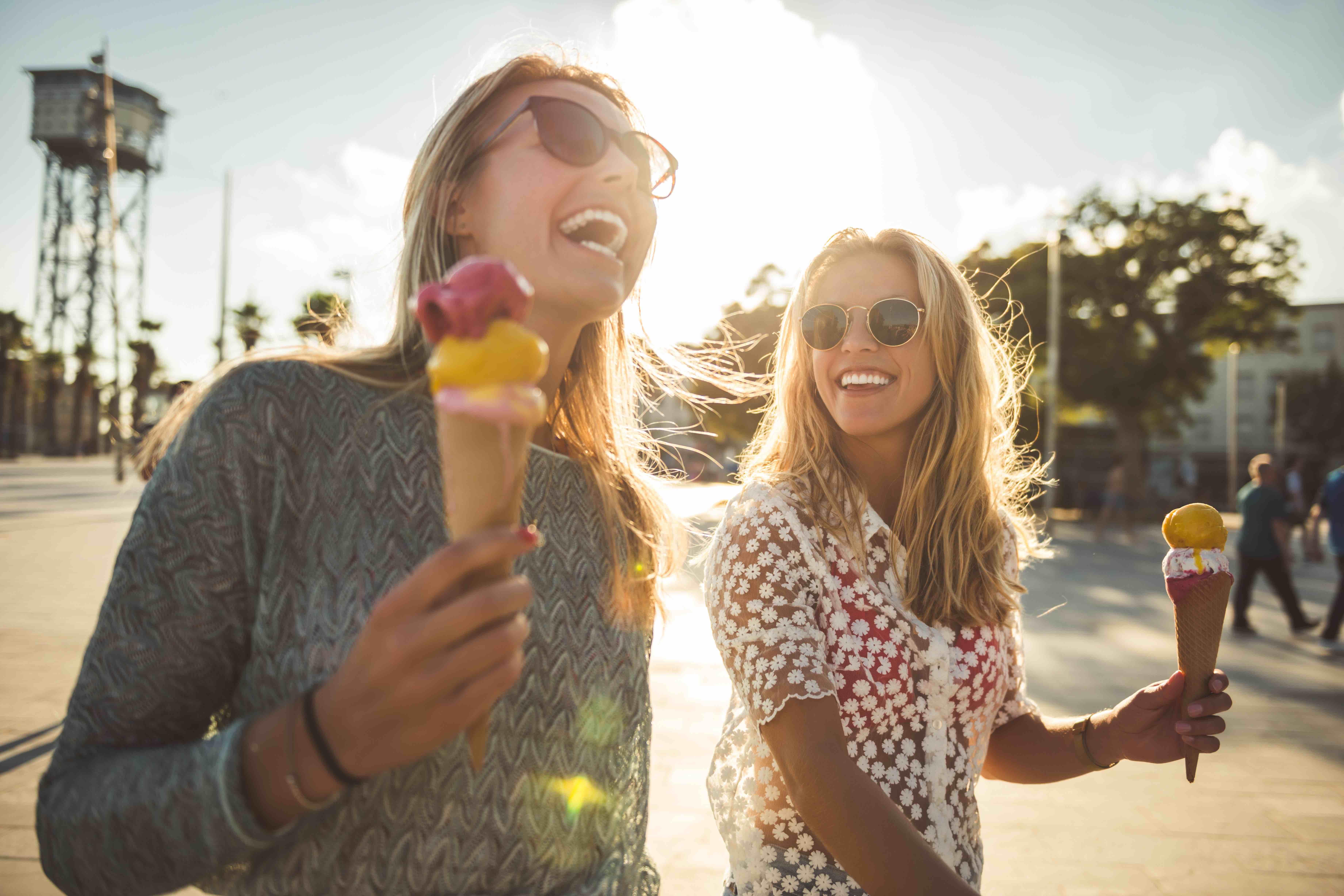 Zwei Frauen gehen in der Sonne spazieren und essen Eis in der Waffel.