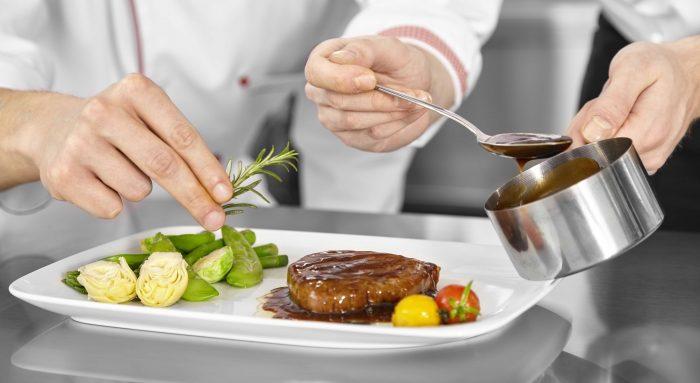 Köche richten ein Steak mit Rosmarin und Sauce an.