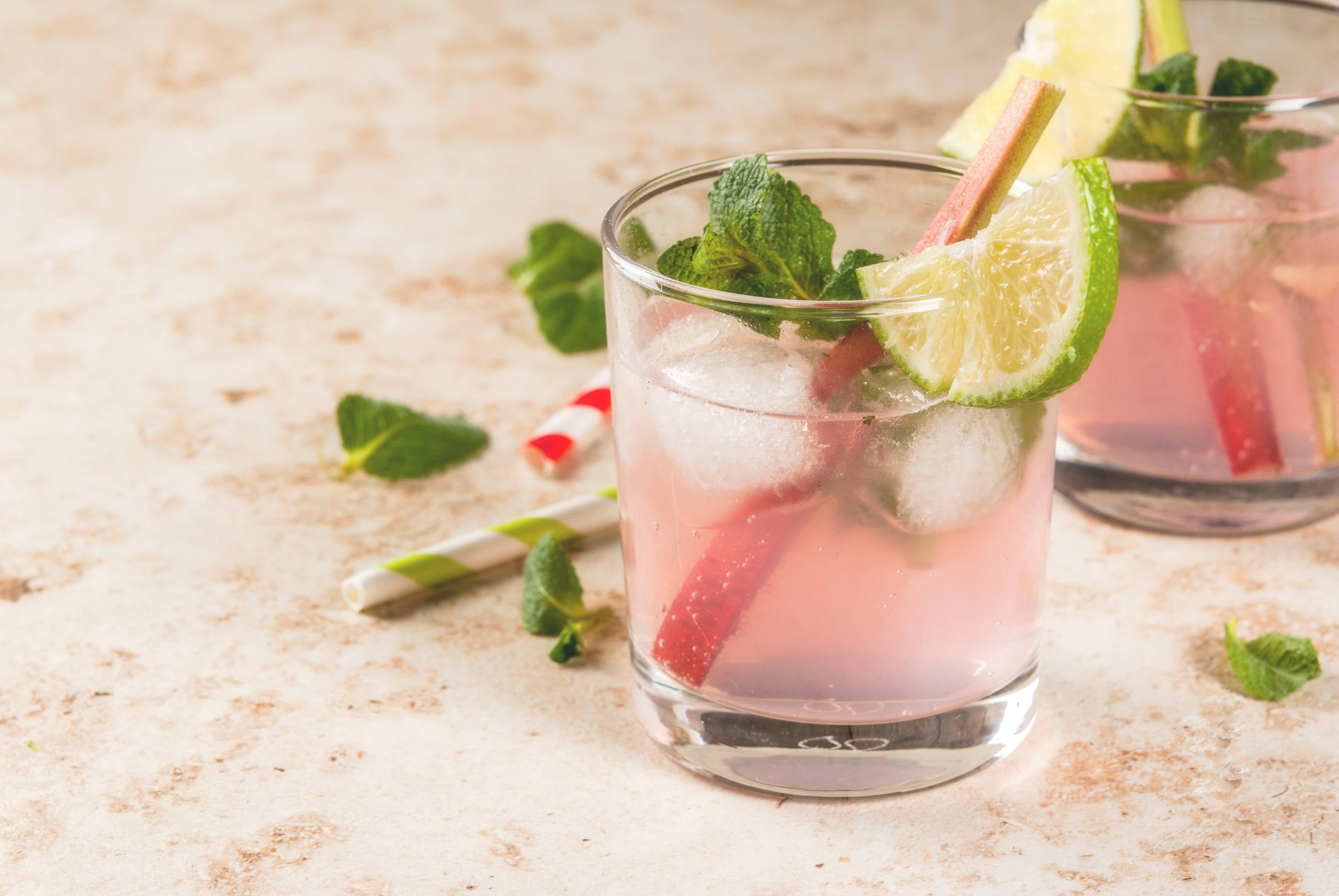 Rhabarber-Limonade im Glas, mit Eiswürfeln und garniert mit Limetten Minze und einer Rhabarberstange.