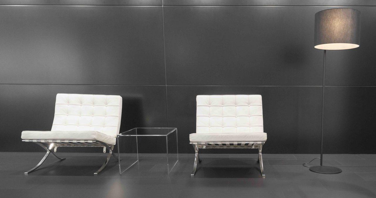 Zwei weiße Barcelona Design Chairs, designt von Mies van der Rohe, neben eine Stehleuchte mit grauem Leuchtenschirm