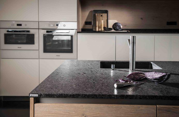 """Küchenarbeitsplatte aus Naturstein """"Silver Pearl"""" mit weißer Einbauküche und eingebautem Backofen im Hintergrund."""