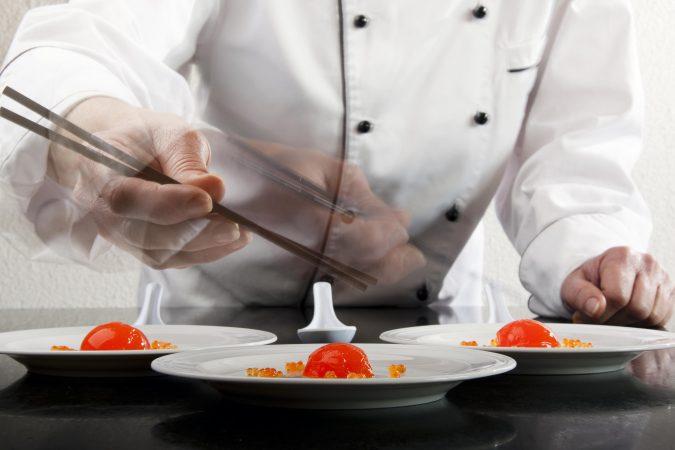 Koch richtet Gerichte der Molekularküche auf weißen Tellern an.