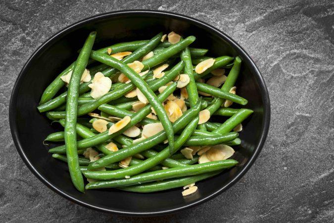 Grüne Bohnen mit gerösteten Mandelplättchen auf einem schwarzen Teller.