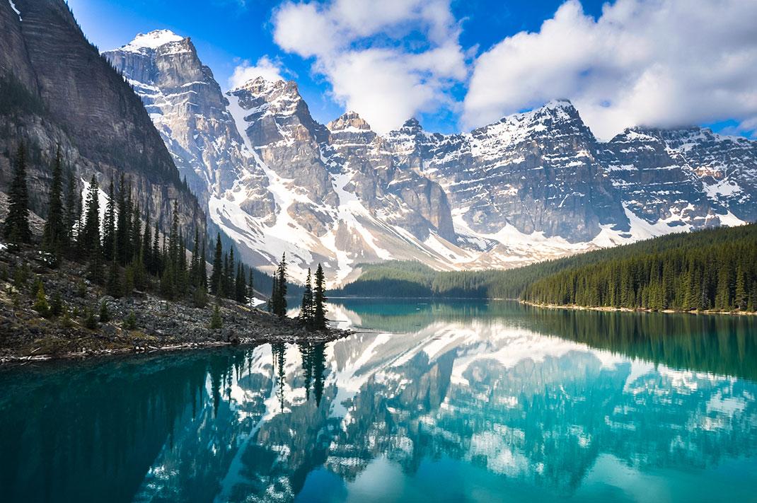 Blauer See mit Wald drumherum und schneebedeckten Bergen im Hintergrund in Kanada.