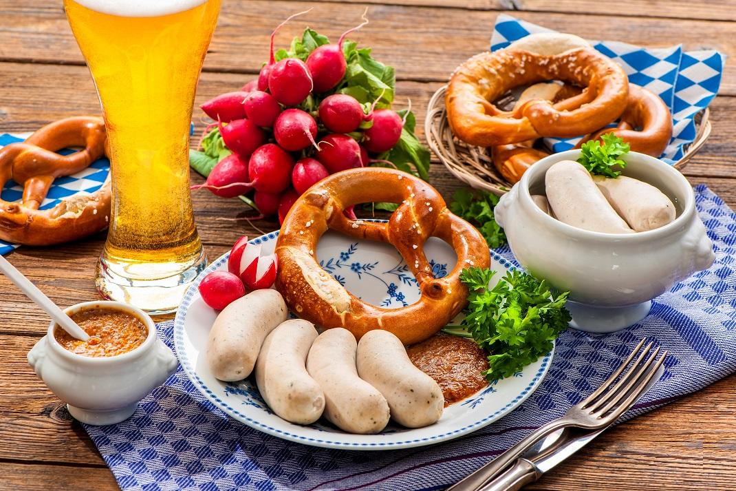 Weißwurstfrühstück mit Weißbier, Radieschen, Brezen, Weißwürsten und süßem Senf.