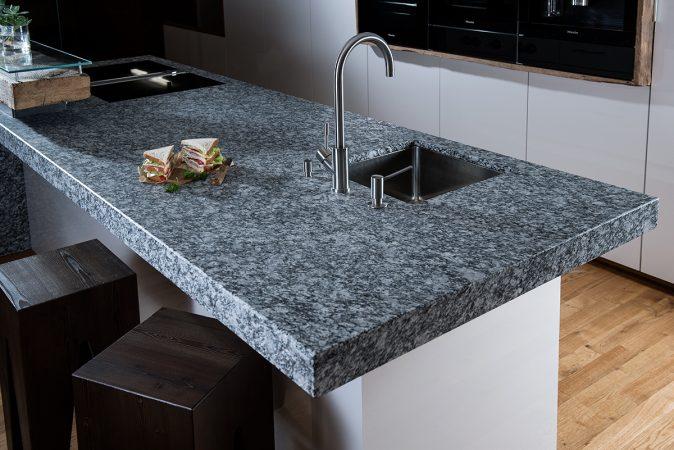 Arbeitsplatte aus Naturstein Alpine White in einer Küche mit weißen Fronten.