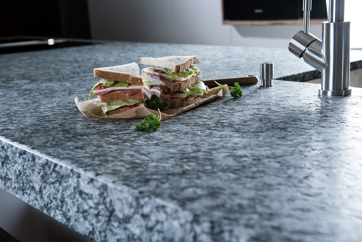 Arbeitsplatte aus Naturstein Alpine White mit einem Sandwich darauf angerichtet.