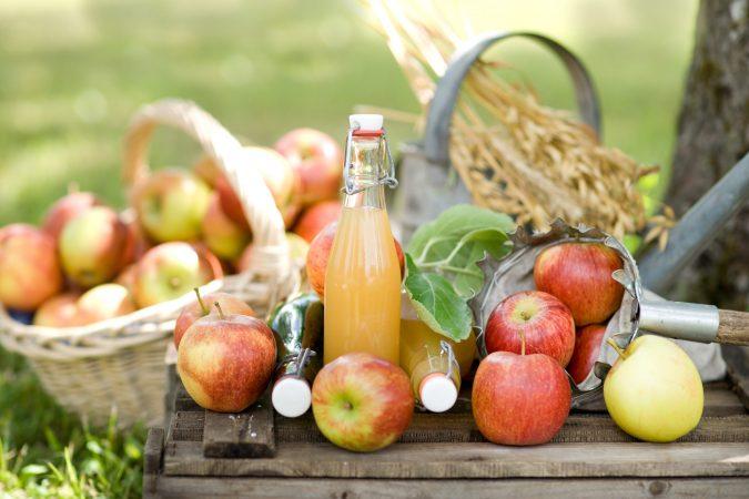 Äpfel und Flaschen mit Most auf einer Holzkiste.