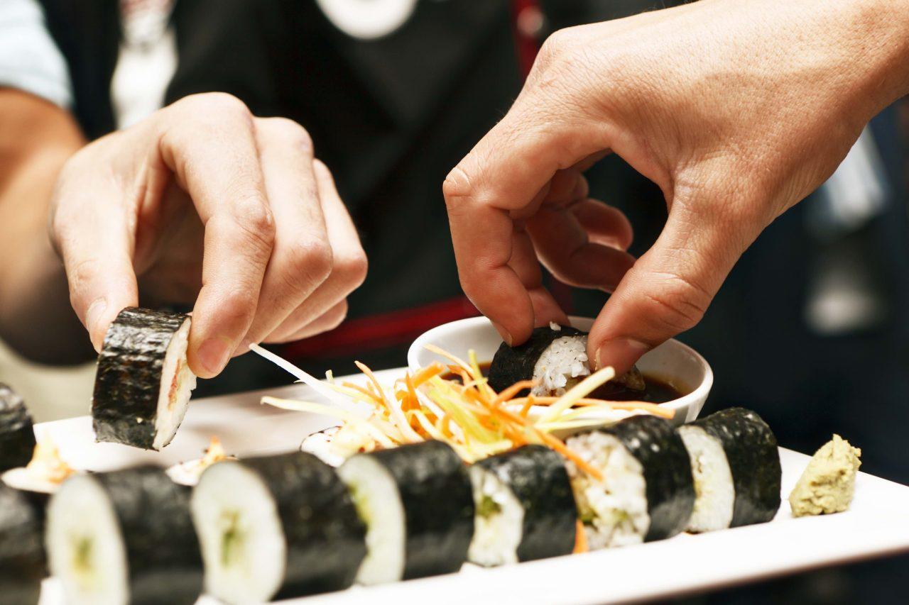 Maki Sushi wird mit der Hand in Sojasauce gedippt.
