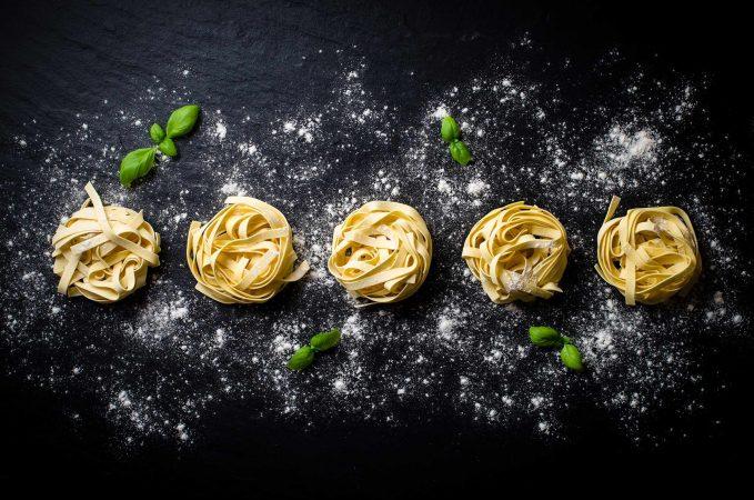 Pasta in Nestern drapiert auf einer Steinplatte, dekoriert mit Mehl und Basilikumblättern.