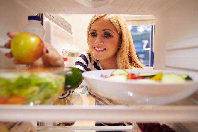 Frau schaut in einen gefüllten Kühlschrank und greift nach einem Apfel.