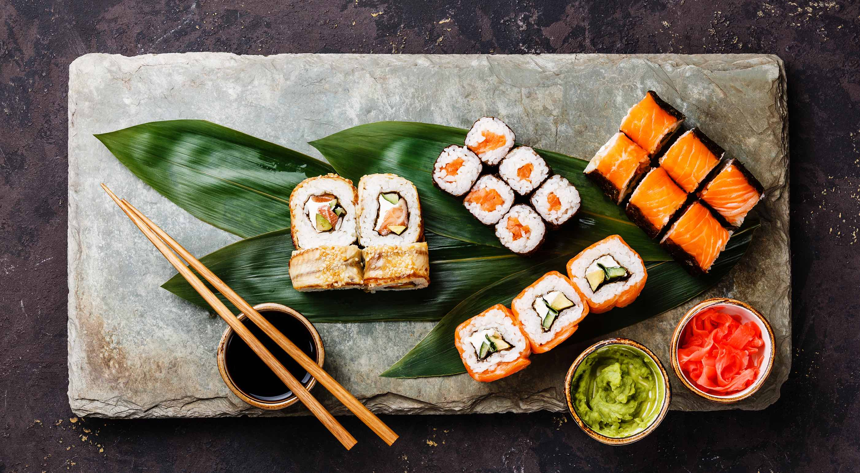 Sushi angerichtet auf einer Steinplatte mit Essstäbchen, Blättern und Schälchen mit Sojasauce, Wasabi und eingelegtem Ingwer.