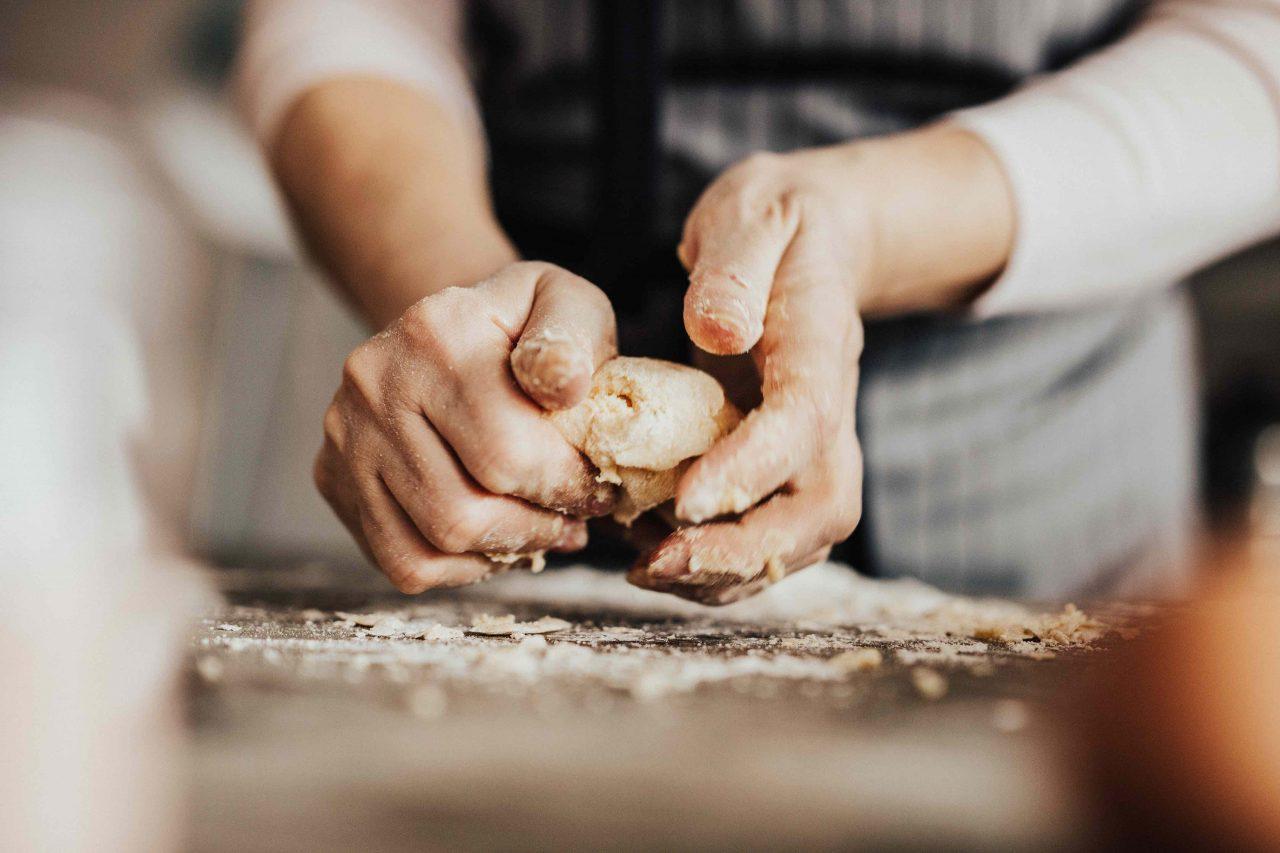 Hände kneten frischen Pasta-Teig auf einer mehlbestäubten Arbeitsfläche.