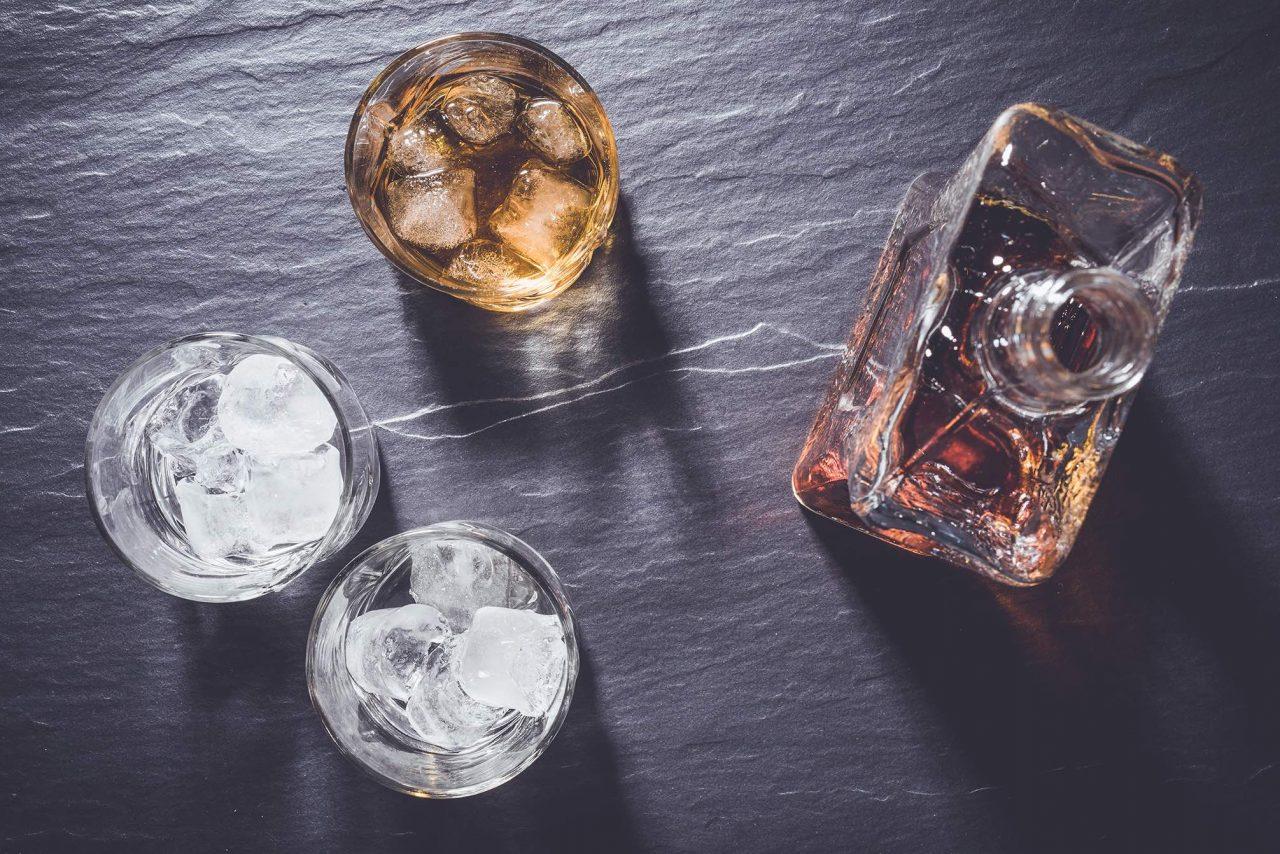 Craft Spirit-Flasche mit Gläsern auf einer Steinplatte