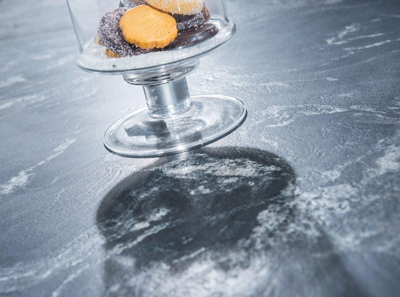 """Küchenarbeitsplatte aus dem Naturstein """"Black Skorpion"""" mit einem Keksglas darauf."""