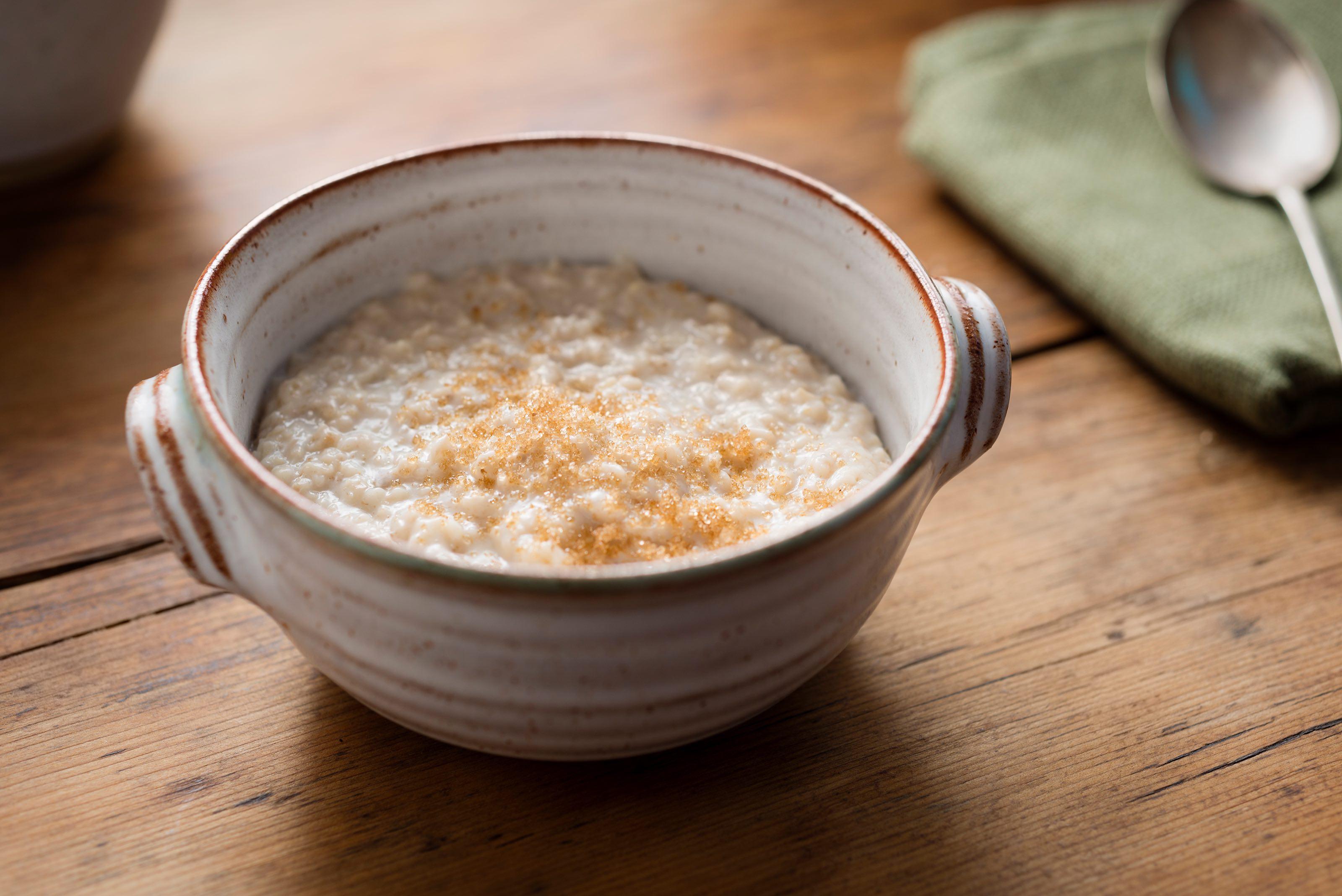 Porridge, bestreut mit Zimt, in einer Schüssel auf einem Holz-Untergrund.
